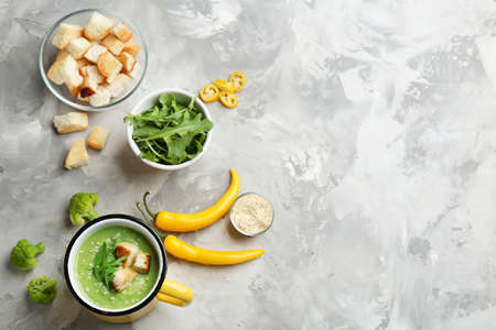Flat lay composition with broccoli cream soup on grey table, space for text