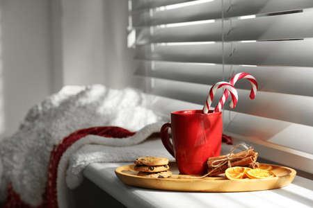 Cup of hot winter drink and treats on windowsill indoors. Space for text Stock Photo