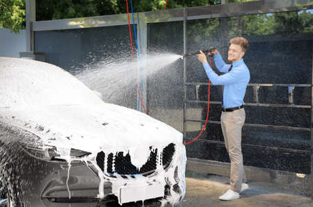 Businessman cleaning auto with high pressure water jet at self-service car wash