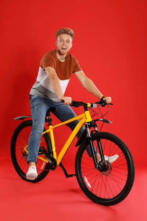 Handsome young man riding bicycle on red background