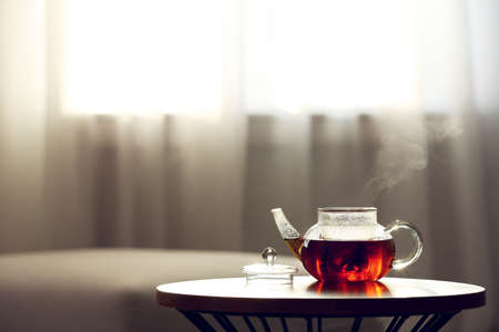 Teapot of fresh hot tea on table against blurred background. Space for text 免版税图像