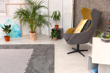 Room interior with armchair and indoor plants. Trendy home decor Imagens