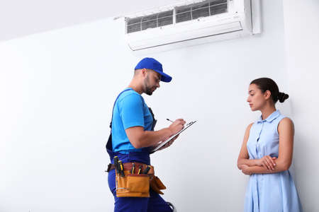 Professional technician speaking with woman about air conditioner indoors Zdjęcie Seryjne