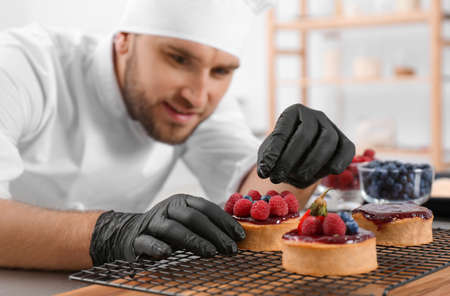 Male pastry chef preparing desserts at table in kitchen Imagens