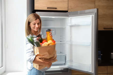 Woman with paper bag full of products near refrigerator in kitchen