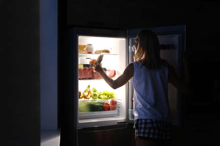Woman taking sandwich out of refrigerator in kitchen at night Zdjęcie Seryjne