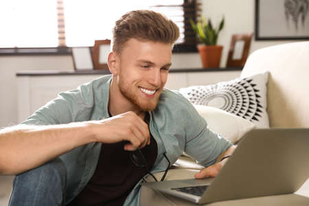 Young man using laptop in living room Stock Photo