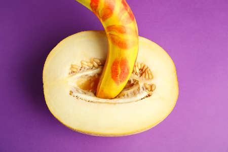 Flat lay composition with fresh banana and melon on purple background. Sex concept 版權商用圖片 - 131461431
