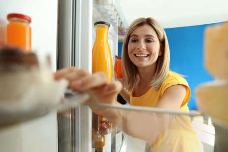 Happy woman taking dessert out of refrigerator in kitchen, view from inside Zdjęcie Seryjne