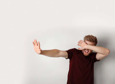 Young man being blinded and covering eyes with hand on light background Stock Photo