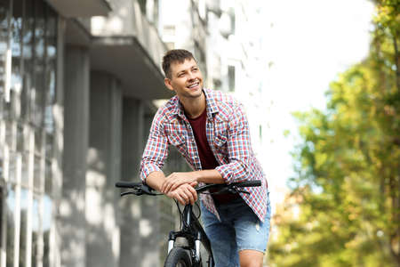 Handsome man with modern bicycle on city street Stok Fotoğraf