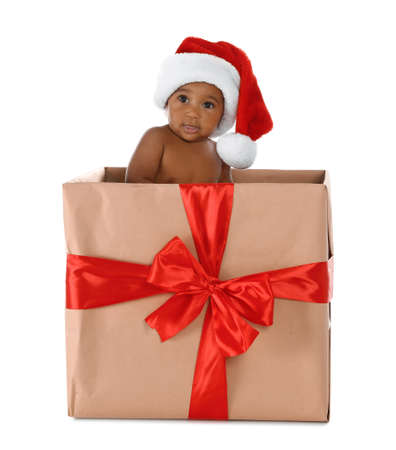 Cute African-American baby wearing Santa hat in Christmas gift box on white background