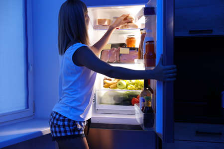 Woman taking products out of refrigerator in kitchen at night