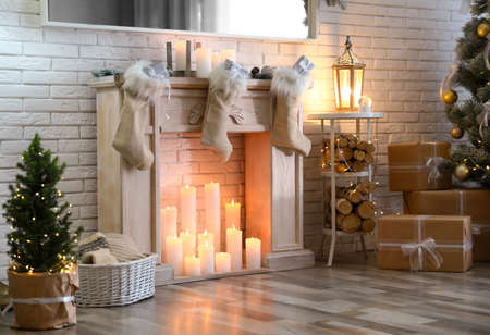 Stylish Christmas interior with decorative fireplace and burning candles