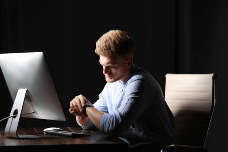 Zmęczony młody człowiek pracujący samotnie w biurze w nocy Zdjęcie Seryjne