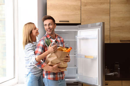 Happy couple with paper bag full of products near refrigerator in kitchen Stock fotó