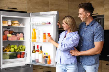 Couple taking bottle with juice out of refrigerator in kitchen Stock fotó