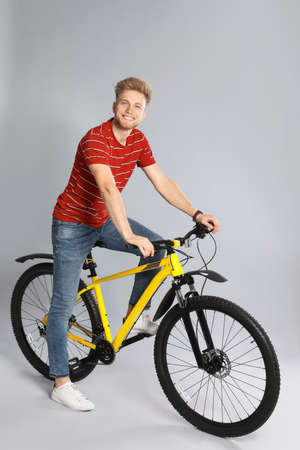 Handsome young man riding bicycle on grey background