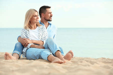 Happy romantic couple spending time together on beach, space for text