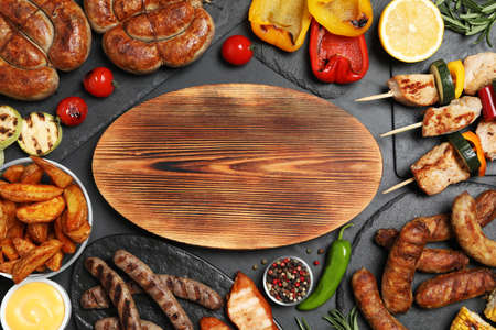 Flat lay composition with barbecued meat and vegetables on grey table. Space for text Stock Photo