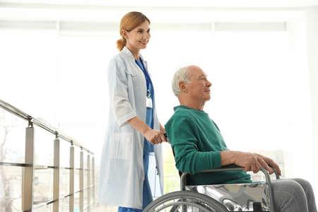 Nurse assisting elderly man in wheelchair indoors