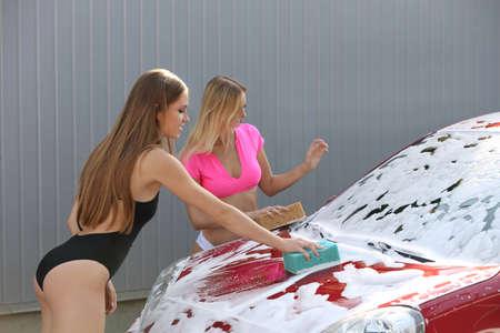 Junge Frauen in Badeanzügen, die Autos mit Schwämmen in der Waschanlage reinigen