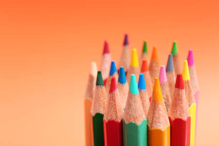 Different color pencils on coral background, closeup. Space for text Stockfoto