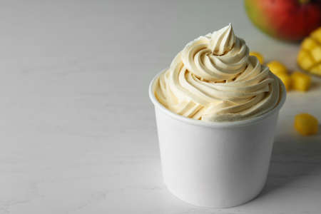 Cup with tasty frozen yogurt on light wooden table. Space for text Banque d'images - 131558394