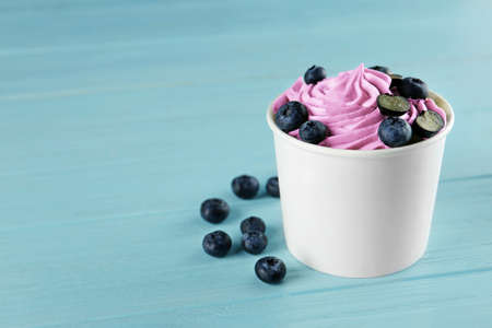 Cup with tasty frozen yogurt and blueberries on blue wooden table. Space for text Banque d'images - 131460767