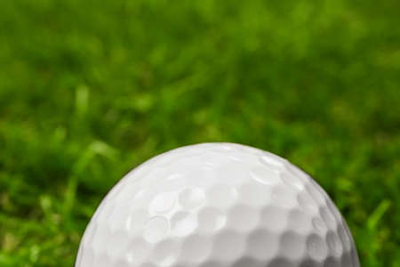 Golf ball on green course outdoors, closeup. Space for text