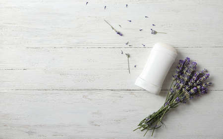 Female deodorant and lavender flowers on white wooden background, flat lay. Space for text Zdjęcie Seryjne