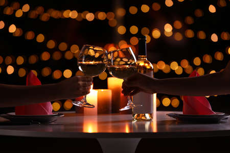 Couple with glasses of wine having romantic candlelight dinner at table, closeup