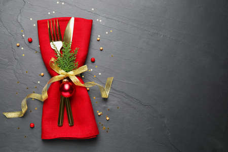 Cutlery set on grey table, top view with space for text. Christmas celebration