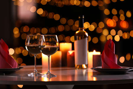 Romantic table setting with glasses of wine and burning candles against blurred background