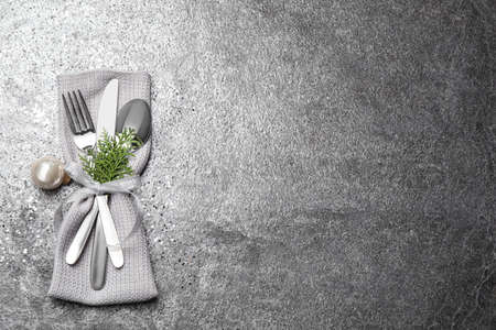 Cutlery set on grey textured table, top view with space for text. Christmas celebration Imagens