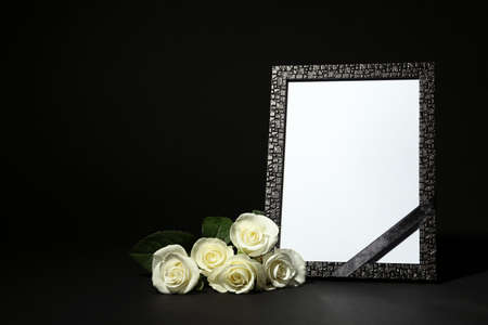Funeral photo frame with ribbon and white roses on dark table against black background. Space for design