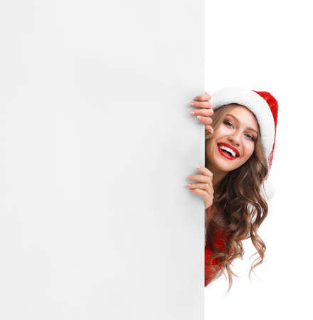 Beautiful Santa girl peeping out of blank banner on white background. Christmas celebration