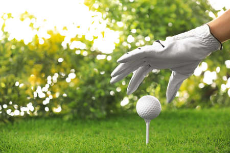 Player putting golf ball on tee at green course, closeup 版權商用圖片