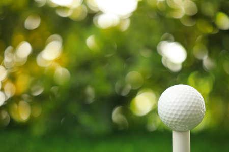 Golf ball on tee against blurred background 版權商用圖片