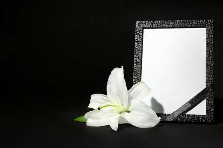 Funeral photo frame with ribbon and white lily on dark table against black background. Space for design