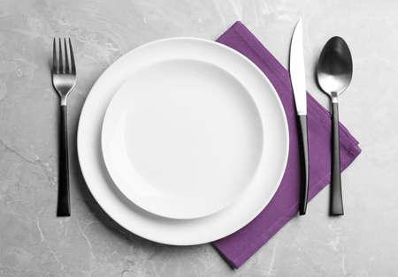 Eleganckie nakrycie stołu na szarym marmurowym tle, płaskie lay Zdjęcie Seryjne