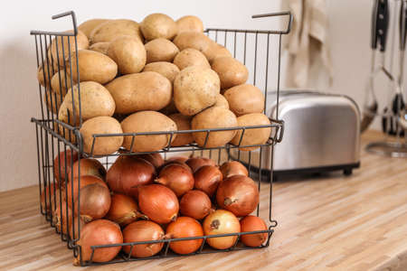Container with potatoes and onions on wooden kitchen counter, space for text. Orderly storage