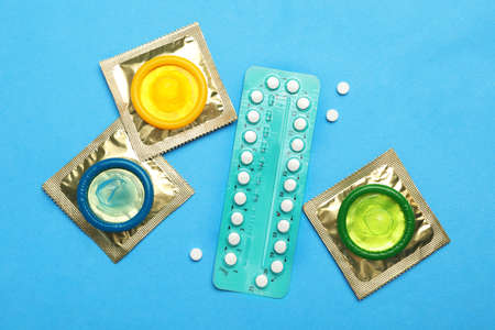Condoms and birth control pills on light blue background, flat lay. Safe sex concept