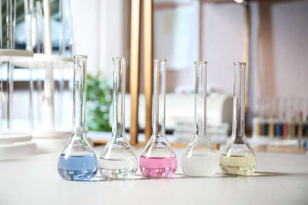 Glassware with colorful liquids on table indoors. Laboratory analysis