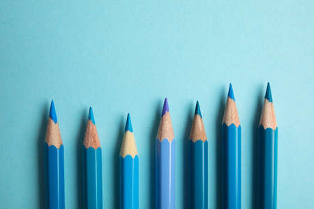 Flat lay composition with color pencils on light blue background