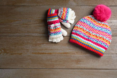 Warm knitted hat and mittens on wooden background, flat lay. Space for text Stock Photo