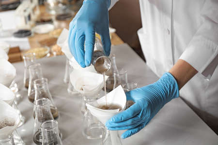 Scientist filtering soil samples at table, closeup. Laboratory analysis