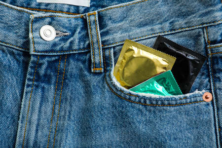 Closeup view of jeans with condoms in pocket. Safe sex concept