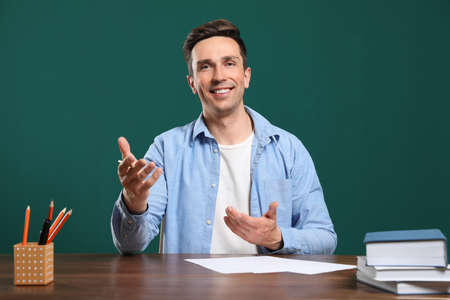 Portrait of male teacher working at table against color background