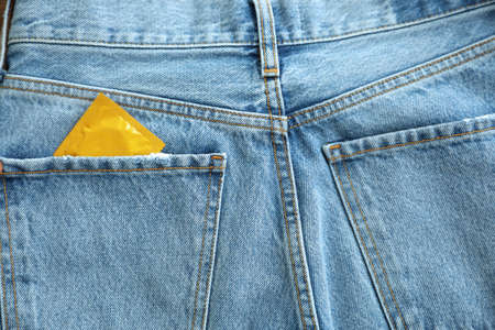 Closeup view of jeans with condom in pocket. Safe sex concept